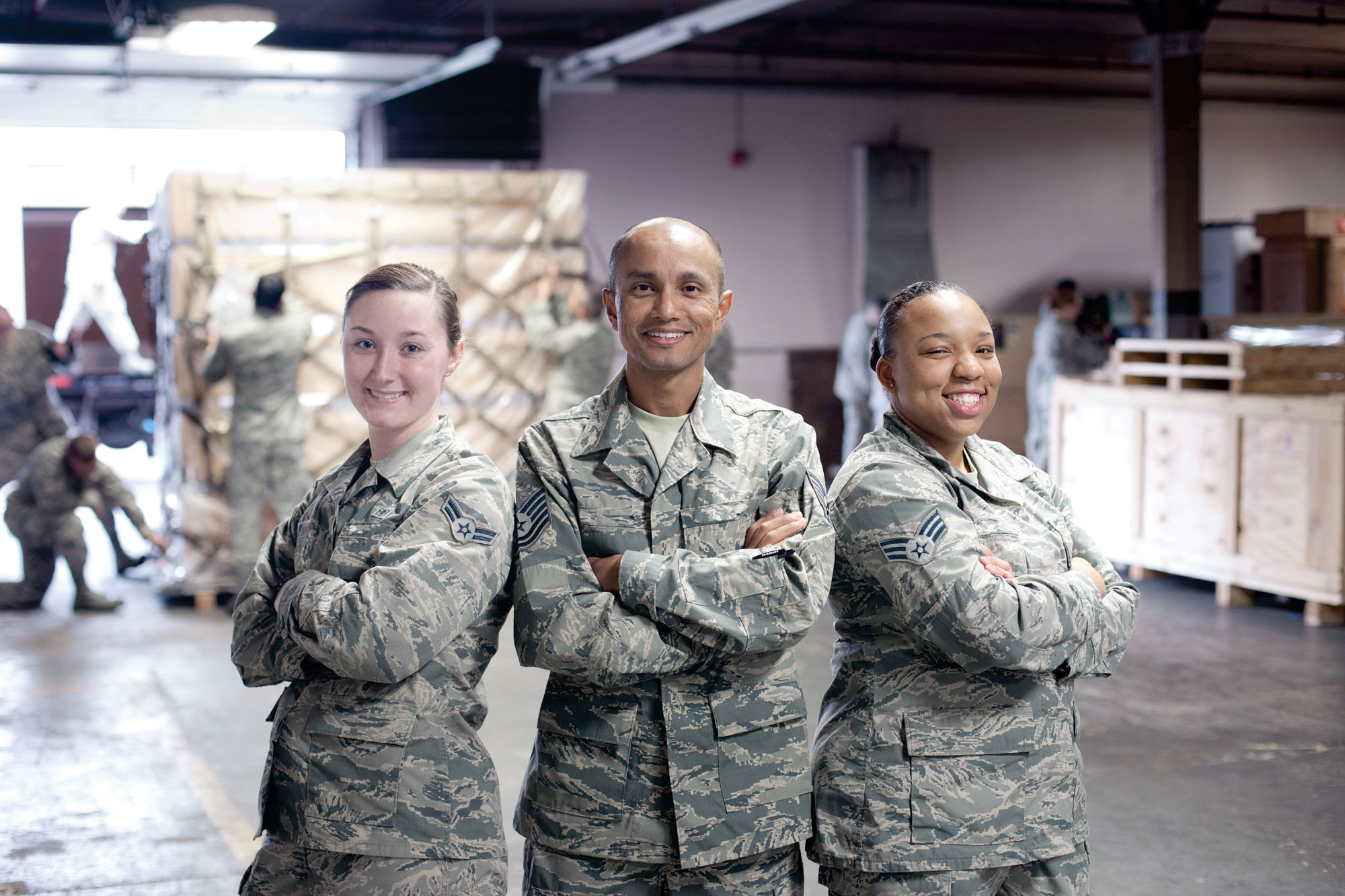 Three members of the Air Force standing together in uniform, smiling.